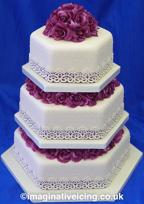 3 tier Hexagonal Ivory Wedding Cake with Plummy Pink Flowers separating each cake and on the Top Tier. Plummy Pink Ribbon round each cake overlaid with Ivory Lace.