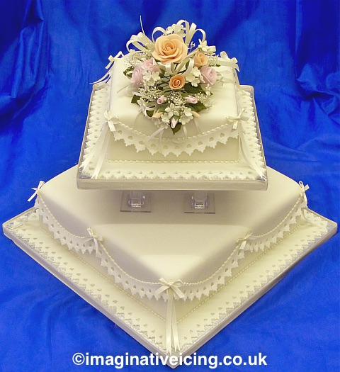 Square Ivory Wedding Cake with delicately coloured sugar flowers, lace effect frills & satin bows